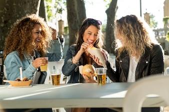 Três belas mulheres jovens que visitam comem mercado na rua.