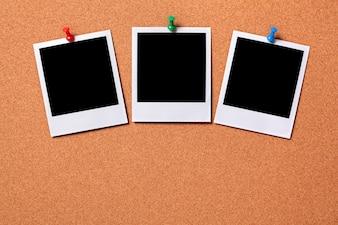 Três fotos do polaroid impressões em uma placa de observação da cortiça