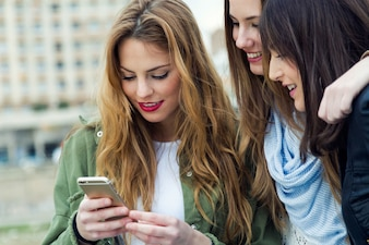 Três mulheres novas que usam um telefone móvel na rua.