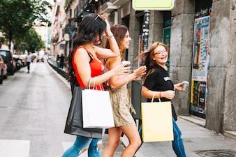 Três mulheres que riem atravessando a rua