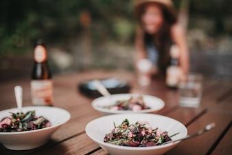 Três pratos de salada em uma mesa, com uma garota em segundo plano.