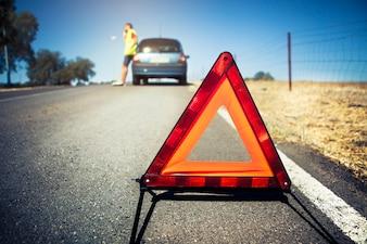 Triângulo de advertência em uma avaria do carro