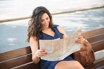 Turista feminino positivo que vê o mapa da cidade no banco