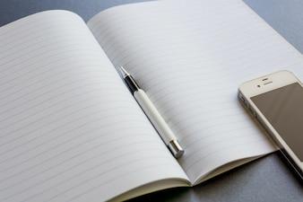 Um caderno aberto com uma pena e um telefone móvel, no fundo cinzento escuro, no trabalho da cena ou no estudo.