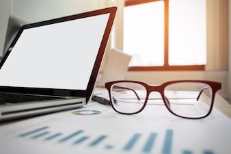 Um caderno, laptop, óculos, mouse, bússola vintage, xícara de café, caneta, papel quadrado (documento) na mesa de escritório (mesa).