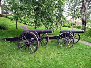 Um canhão de ferro fundido em um carro pequeno