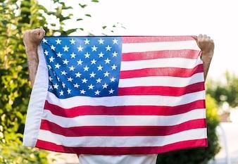 Um homem segurando com ambas as mãos a bandeira americana, para o dia memorial de 4 de julho