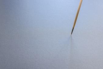 Uma escova de pintura tiped fina que está vertical, isolado no fundo cinzento.