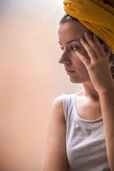 Uma linda garota triste e solitária sentada perto da janela está faltando. Sozinho tristeza pensativa garota está triste na janela