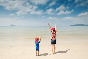 Uma mãe e filho na praia ao ar livre Mar e céu azul