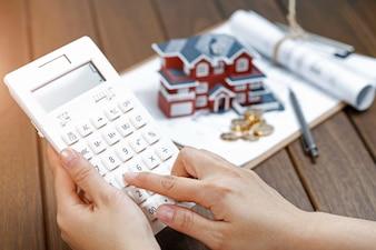 Uma mão feminina operando uma calculadora na frente de um modelo de casa de Villa