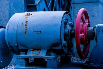 Uma máquina antiga; uma caixa de motor; um objeto giratório
