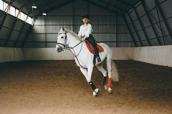 Uma menina a cavalo montando uma arena