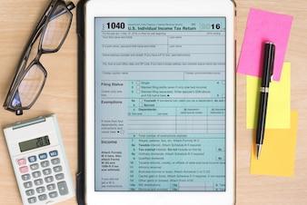 US Formulário de imposto 1040 em comprimido com calculadora e caneta