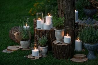 Vasos altos com velas brancas estão nos blocos do jardim