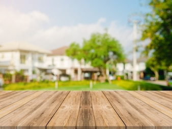 Vazio topo de mesa de madeira no borrão resumo verde do jardim e da casa na manhã background.For montagem produto exibição ou design layout visual chave