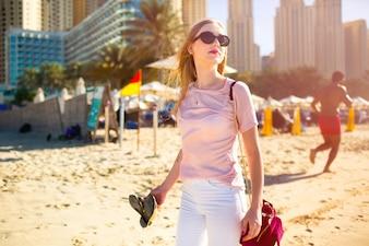 Vento sopra o cabelo da mulher enquanto ela caminha ao longo da praia em Dubai ensolarado