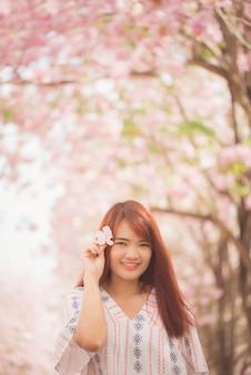 Viajante de mulher feliz, relaxe, sinta-se livre com flores de cerejeira ou árvore de flor de sakura em férias