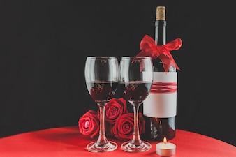 Vidros de vinho com rosas e uma garrafa atrás