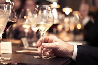 Vinho branco à mão com jantar no restaurante