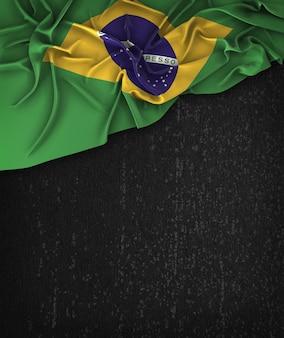 Vintage da bandeira de Brasil em um quadro preto do Grunge com espaço para o texto