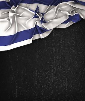 Vintage da bandeira de Israel em uma tabela preta do Grunge com espaço para o texto