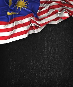 Vintage da bandeira de Malaysia em um quadro preto do Grunge com espaço para o texto