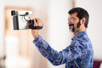 Vintage young man filmando em fundo não focado