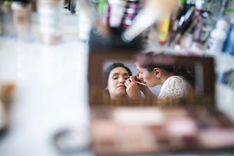 Visagiste aplicando maquiagem