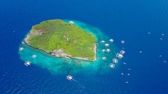 Vista aérea da praia arenosa com turistas que nadam na linda água do mar clara da ilha de Sumilon, pousando na praia perto de Oslob, Cebu, Filipinas. - Aumentar o processamento de cores.