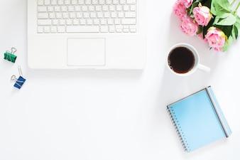 Vista aérea do laptop do computador, uma xícara de café, rosas e caderno no fundo branco, Copiar espaço