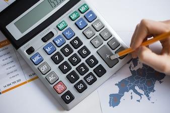 Vista colhida da mão do homem que trabalha com calculadora