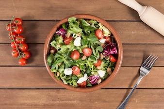 Vista de cima da superfície de madeira com deliciosa salada