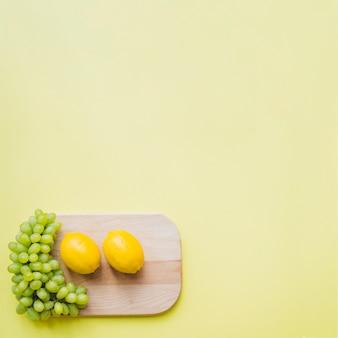 Vista de cima da tábua de corte com limões e cacho de uvas