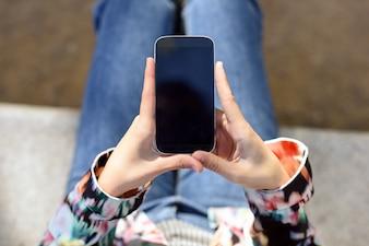 Vista de cima de uma mulher segurando um telefone móvel