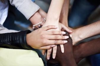 Vista de cima dos jovens juntando as mãos.