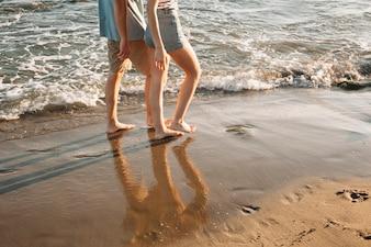 Vista de pé de casal andando na praia