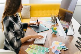 Vista lateral do designer gráfico na mesa