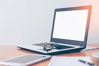 Vista lateral do desktop do escritório com laptop em branco e várias ferramentas de escritório