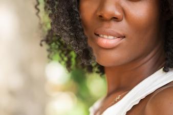 Vista recortada da mulher negra bonita ao ar livre