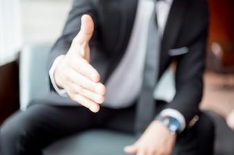 Vista recortada do braço extensível do homem para Handshake