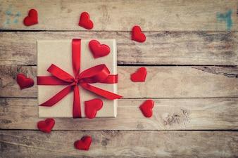 Vista superior (acima) caixa de presente e fita vermelha e coração vermelho para valentine na mesa de madeira. Fundo dos Namorados.