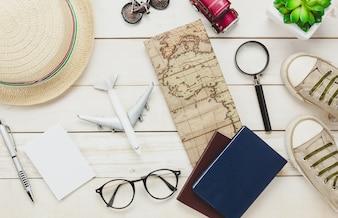 Vista superior dos itens de viagem essenciais. O cartão de caderno dos sapatos passa pelo mapa