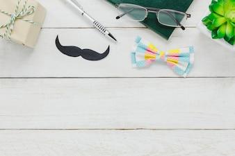 Vista superior Happy Father day.accessories com árvore, bigode, gravata vintage, presente, caneta, caderno e óculos em fundo de madeira branca rústica.
