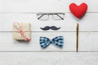 Vista superior Happy Father day.flat lay acessórios com coração vermelho, bigode, gravata vintage, presente, caneta em fundo de madeira branca rústica.