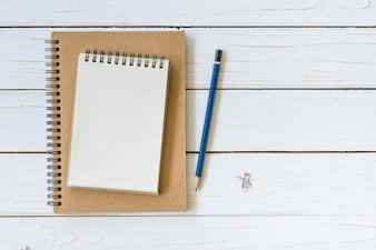 Vista superior livro aberto sobre mesa de madeira com lápis.