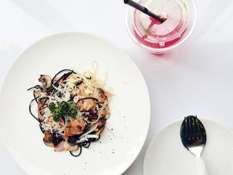 Vista superior macarrão espaguete com tomate e salsa na mesa branca.