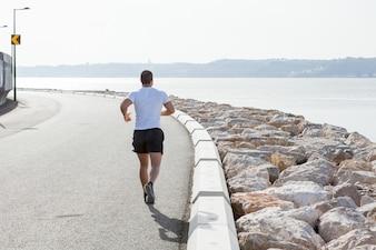 Vista traseira do homem forte que corre na estrada do beira-mar