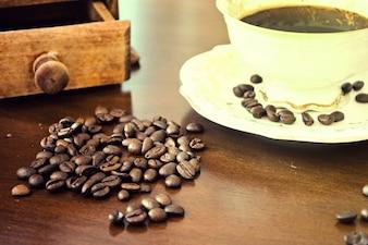 Xícara de sementes de café e de café