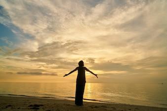 Yoga e mulher na praia